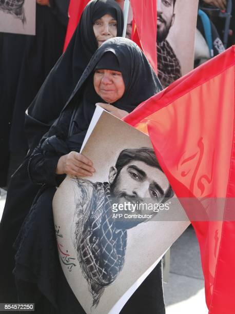 A mourner holds a portrait of Mohsen Hojaji a young member of Iran's elite revolutionary guards Corps who was beheaded in Syria by Islamic State...