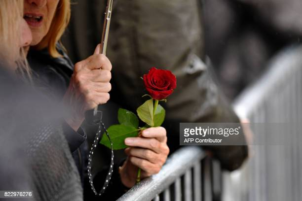 A mourner holds a rose as requested by the family as she arrives for the funeral service of Manchester Arena bomb victim SaffieRose Roussos at...