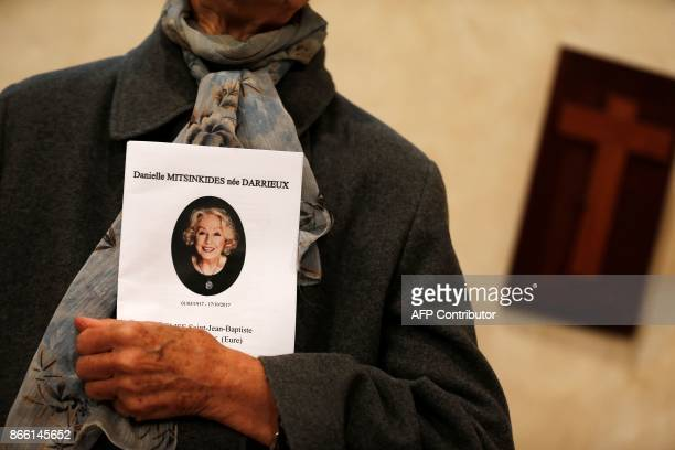 A mourner holds a service sheet as she attends the funeral service of the French actress Danielle Darrieux in BoisleRoi northwestern France on...