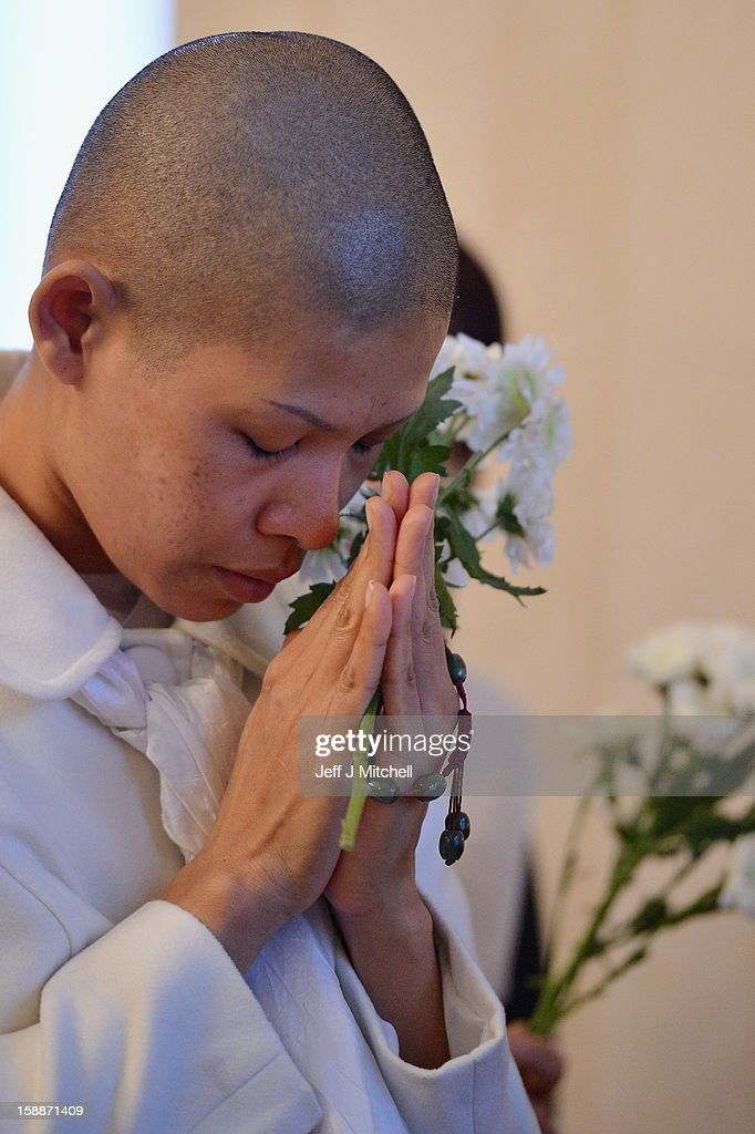 A mourner holds flowers and grieves at a service of remembrance for three Thai Buddhist Monks who died in a car crash on Christmas Eve, at Oakvale Funeral Home on January 2, 2013 in Edinburgh, Scotland. Abbot Phramaha Pranom Thongphaiboon, 43, head of the Thai Buddhist community in Aberdeen, was killed in a car crash on Christmas Eve along with his colleagues Phramaha Kriangkrai Khamsamrong, 35, and Phramaha Chai Boonma, 36. The three men were travelling to the Dhammapadipa Temple in Edinburgh when they were involved in the head-on collision on the A68 near Pathhead, Midlothian.