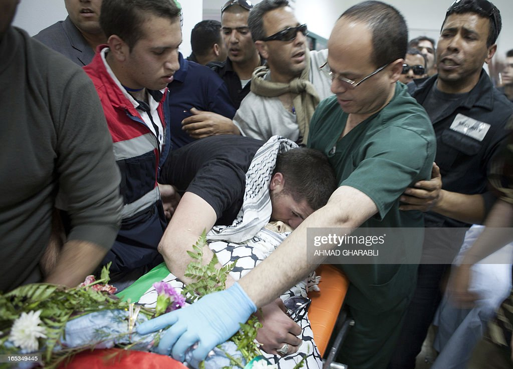 A mourner, kisses the body of Palestinian prisoner Maisara Abu Hamdiyeh as the corpse arrived for a Palestinian autopsy at the medical centre of the Abu Dis University, on the outskirts of Jerusalem, on April 3, 2013. Hamdiyeh, who had served 10 years of a life sentence for attempted murder, died in an Israeli hospital the previous morning two months after being diagnosed with throat cancer. AFP PHOTO/AHMAD GHARABLI
