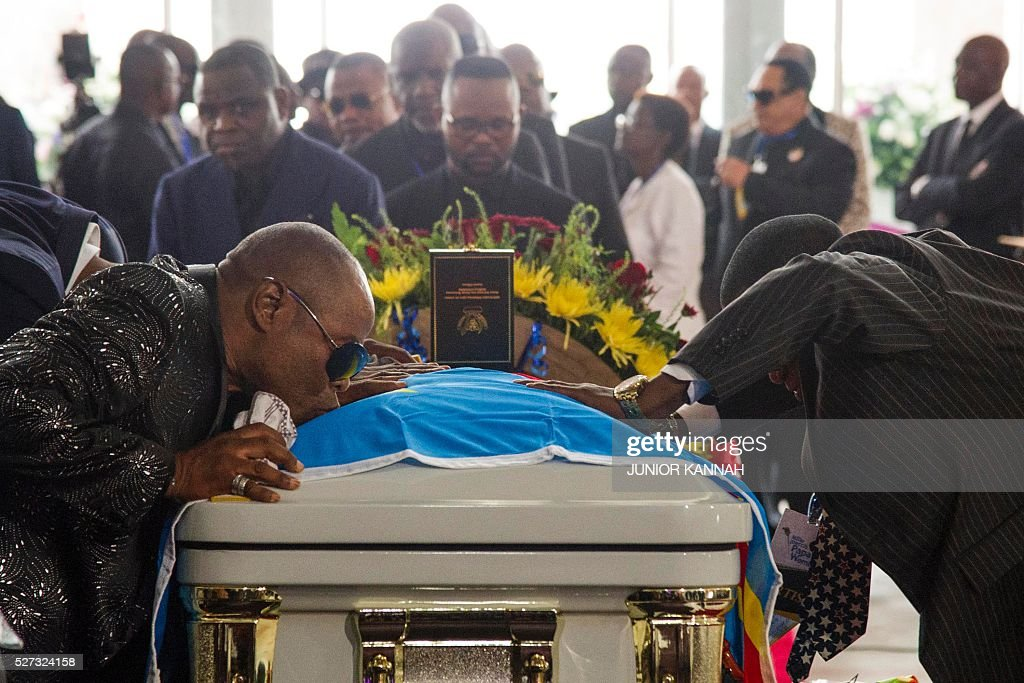 A mourner kisses the coffin of rumba musician Papa Wemba during his funeral in Kinshasa on May 2, 2016. Democratic Republic of Congo's rumba king Papa Wemba was posthumously awarded one of his country's highest honours, a week after he collapsed on stage and died aged 66. / AFP / JUNIOR