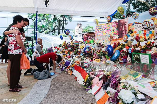 A mourner left cries next to a floral tribute to Singapore's first elected Prime Minister Lee Kuan Yew following the announcement of his death at...