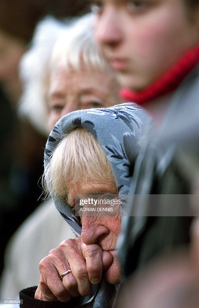 A mourner listens to the funeral service for Reggie Kray outside St. Matthew's Church in Bethnal Green in East London 11 October 2000. Kray, who died of cancer 10 days ago shortly after being released from prison, was one of Britain's most feared gangsters who held a mafia-like grip on London's East End during the 1960's. Reggie Kray and his twin brother Ronnie were convicted of murder and sentenced to life in 1969.