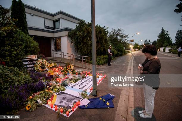 A mourner looks to flowers candels and a portrait of Helmut Kohl in front of the home of former German Chancellor Helmut Kohl in Oggersheim district...