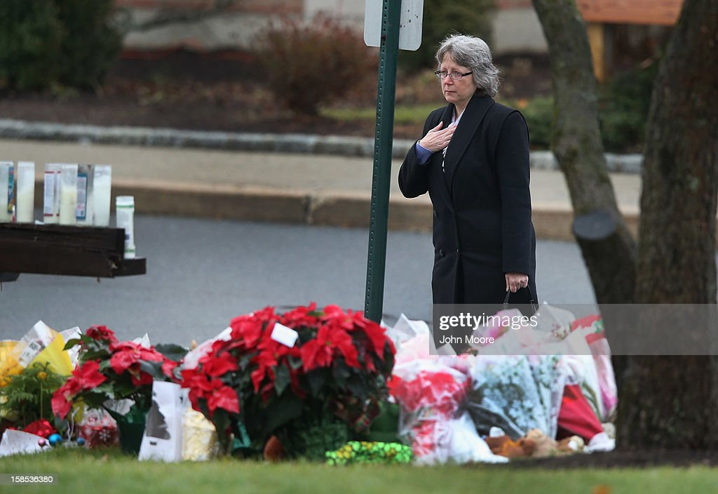 A mourner pays respects at a makeshift memorial following a funeral for Jessica Rekos at the St. Rose of Lima Catholic church on December 18, 2012 in Newtown, Connecticut. Funeral services were held at the church for both Jessica Rekos and James Mattioli, 6, Tuesday, four days after 20 children and six adults were killed at Sandy Hook Elementary School.