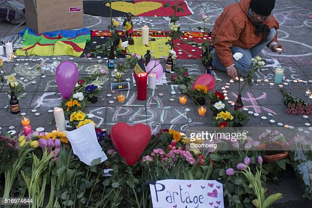 A mourner places a candle next to flowers and floral tributes at Beursplein square in Brussels Belgium on Tuesday March 22 2016 Explosions ripped...