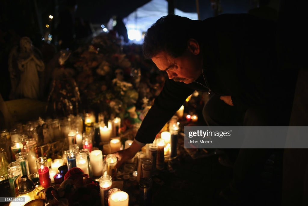 A mourner places a candle while visiting a makeshift memorial for shooting victims on December 18, 2012 in Newtown, Connecticut. Funeral services were held in Newtown Tuesday for Jessica Rekos and James Mattioli, both age six, four days after 20 children and six adults were killed at Sandy Hook Elementary School.
