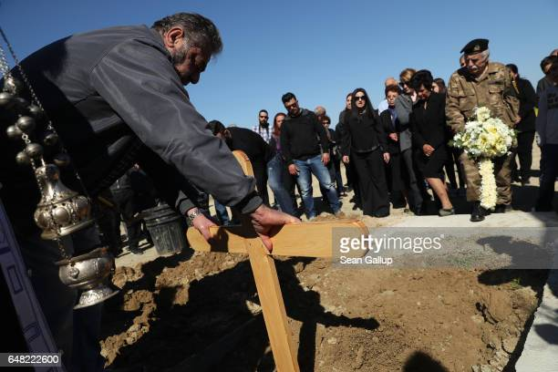 A mourner places a cross onto the fresh grave of Georgiou Theodoulos Theodoulou as soldiers and mourners look on at Theodoulou's funeral on March 5...