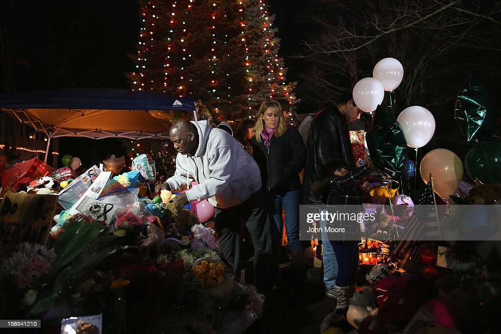 A mourner places a stuffed animal while visiting a makeshift memorial for shooting victims on December 18, 2012 in Newtown, Connecticut. Funeral services were held in Newtown Tuesday for Jessica Rekos and James Mattioli, both age six, four days after 20 children and six adults were killed at Sandy Hook Elementary School.