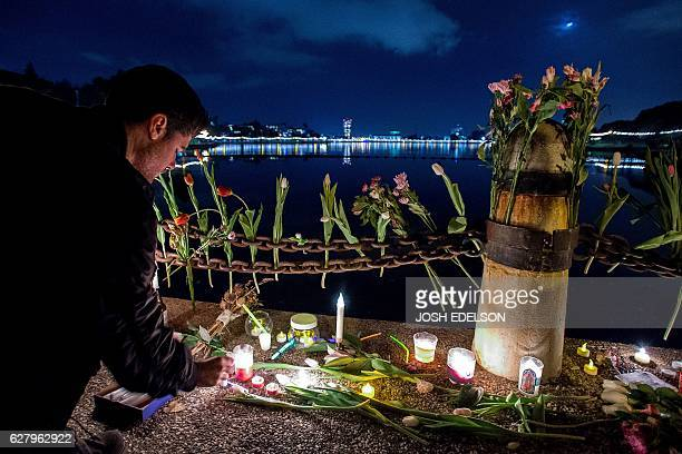 A mourner places flowers and candles during a vigil honoring those who died in a warehouse fire in Oakland California on December 5 2016 The death...