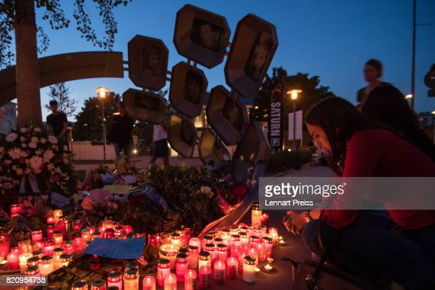 A mourner prays at a memorial to commemorate the victims of the shooting spree that one year ago left ten people dead including the shooter on July...