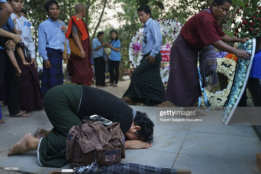 A mourner prays in front of Win Tin's tombstone during his memorial service in Yay Way cemetery on April 23, 2014 in Yangon, Burma. The Burmese journalist who helped Aung San Suu Kyi launch a pro-democracy movement against the junta military regime, died April 21 in Rangoon.