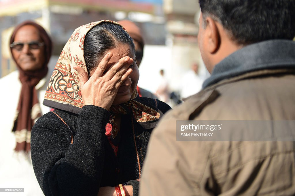 A mourner reacts as she pays tribute at a memorial outside the Swaminarayan Vidhyalaya on the twelfth anniversary of the Gujarat earthquake in Ahmedabad on January 26, 2013t. Some 32 students of this school died in the quake that killed over 19,000 people. AFP PHOTO / Sam PANTHAKY