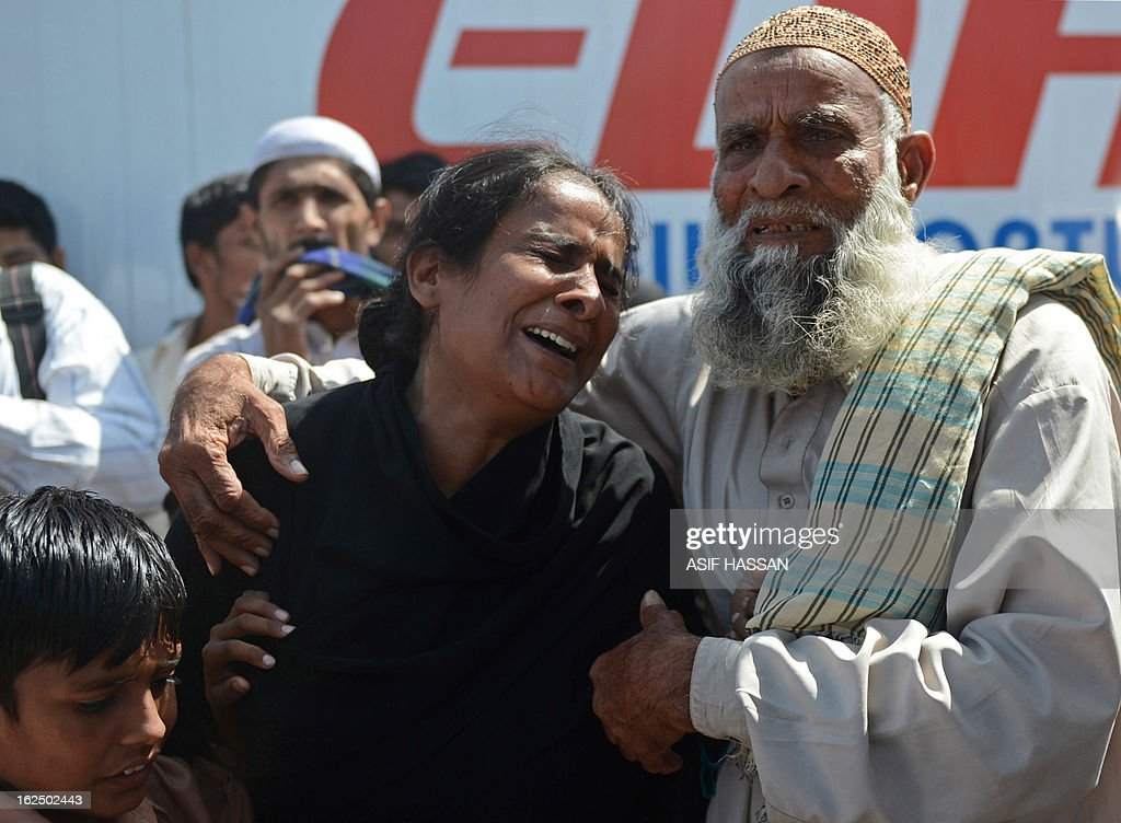 A mourner reacts during the funeral of garment factory fire victims, their bodies released by authorities after months of forensics investigations following their deaths in the incident September last year, during a funeral in Karachi on February 24, 2013. Pakistani police have moved to drop murder charges against the owners of a garment factory where 289 workers were killed in a fire in September 2012, the mens' lawyer said February 11. AFP PHOTO/Asif HASSAN