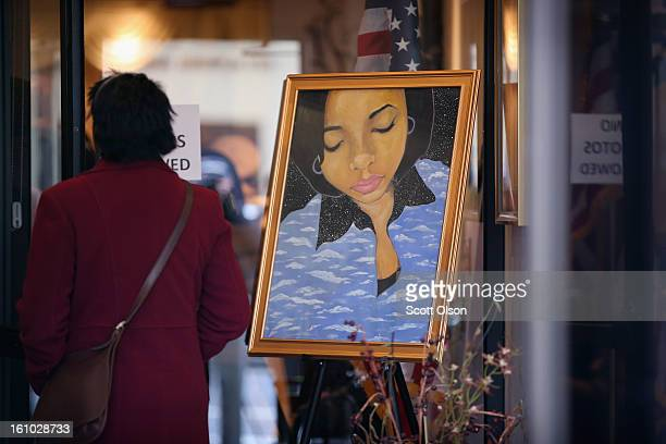 A mourner stands next to a painting of 15yearold Hadiya Pendleton placed at the entrance of the Calahan Funeral Home during her wake on February 8 in...