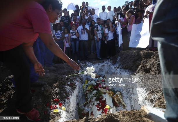 A mourner tosses flowers during the burial of Vanessa dos Santos who was shot in the head and killed in the doorway of her house during a shootout...