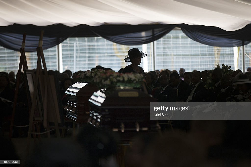 A mourner walks past coffins during a funeral service for Kenyan President Uhuru Kenyatta's nephew Mbugua Mwangi and his fiancee Rosemary Wahito who were killed at the the Westgate Mall terrorist attack, on September 27, 2013 in Nairobi, Kenya. The country is observing three days of national mourning as security forces begin the task of clearing and securing the Westgate shopping mall following a four-day siege by militants.