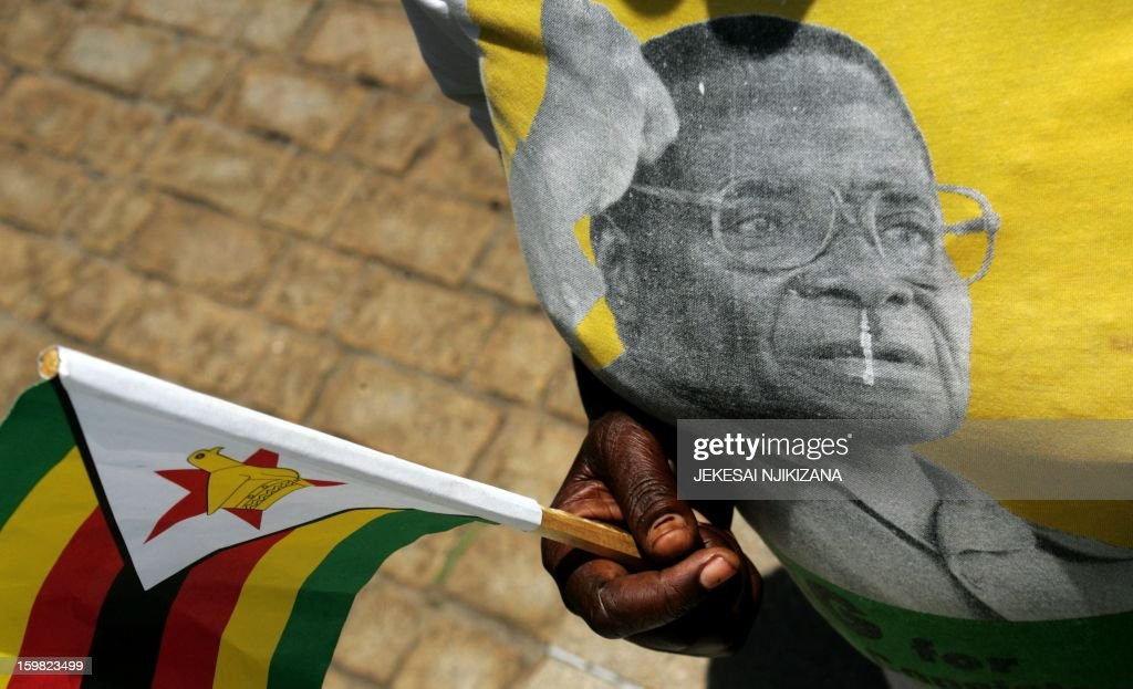 A mourner wears regalia bearing the face of Zimbabwe President Robert Mugabe during the burial of the late vice-president John Landa Nkomo at the National Heroes Acre, in Harare, on January 21, 2013. President Mugabe called for a peaceful election. Nkomo, 78, died at St. Anne's hospital in Harare on January 17. Responsible for overseeing financial, economic and environmental policy Nkomo, a former speaker of parliament, was seen as loyal to Mugabe. AFP PHOTO / Jekesai Njikizana