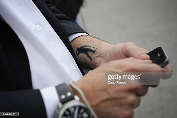Mourner with the iconic image of Severiano Ballestors tattooed checks his mobile phone during the funeral service held for legendary Spanish golfer...