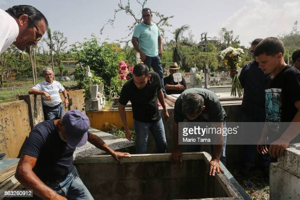 Mourners and cemetery workers gather at the gravesite of Wilfredo Torres Rivera who died October 13 after jumping off a bridge into a lake three...