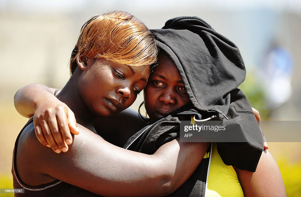 Mourners are seen after a train rammed into a public service bus in Nairobi October 30, 2013. The accident happened at a crossing point killing at least 12 passengers in the bus. The train crashed into the side of the bus as it crossed the railway line during the peak hours of morning rush hour, local police commander Benjamin Nyamae said. AFP PHOTO/John MUCHACHA
