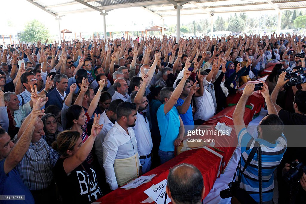 Mourners are seen during a funeral ceremony for the victims of a suicide bomb attack yesterday which killed 32 people in the southern Turkish town of...