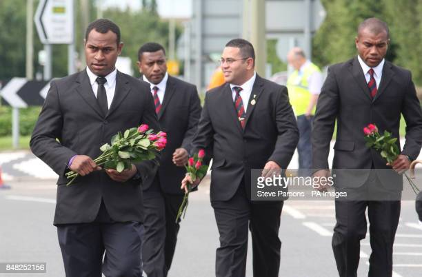 Mourners arrive carrying flowers as they join friends and families of Guardsman Craig Roderick and Guardsman Apete Saunikalou Ratumaiyale Tuisovurua...