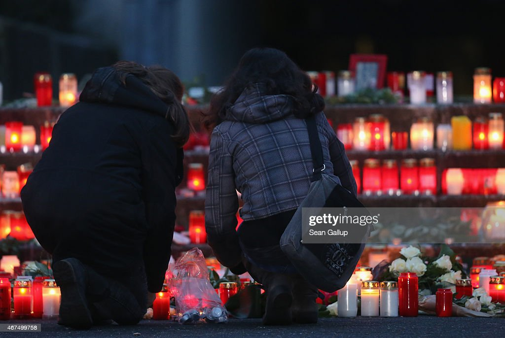Mourners arrive to lay flowers and candles at a makeshift memorial at the JosephKoenigGymnasium high school to 16 students and two teachers from the...