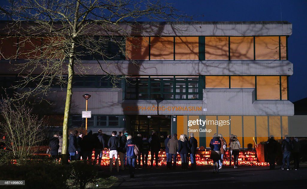 Mourners arrive to lay flowers and candles outside the JosephKoenigGymnasium high school to pay tribute to 16 students and two teachers from the...