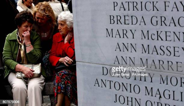 Mourners at the memorial on Talbot Street to the 1974 Dublin and Monaghan Bombings on the anniversary day of the bombings run water onto the footpath...
