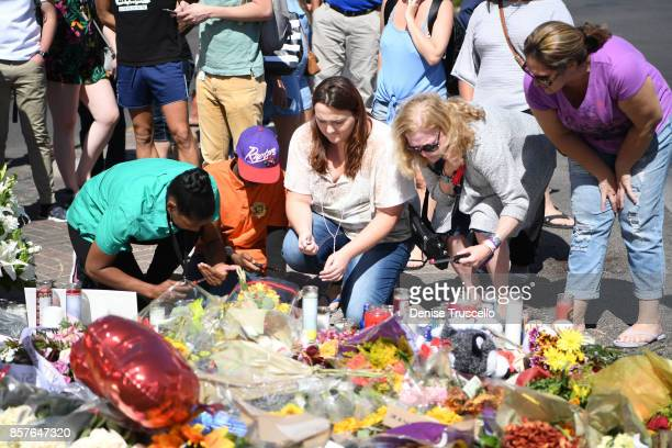 Mourners attend a memorial on Las Vegas Boulevard and Reno Avenue for the victims of the Route 91 Harvest country music festival shootings On October...