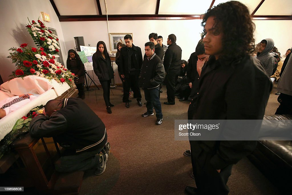 Mourners attend a wake for Rey Dorantes on January 17, 2013 in Chicago, Illinois. Fourteen-year-old Rey Dorantes died after being shot 6 times while he was sitting on the front porch of his home talking on the phone on January 11. Dorantes' murder was the 21st homicide recorded in Chicago for 2013, a city which saw more than 500 homicides in 2012.