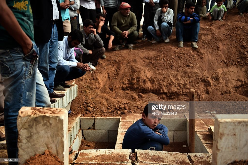 Mourners attend on October 11 2014 in the Turkish town of Suruc in Sanliurfa province the funeral of Syrian Kurdish People's Protection Units...