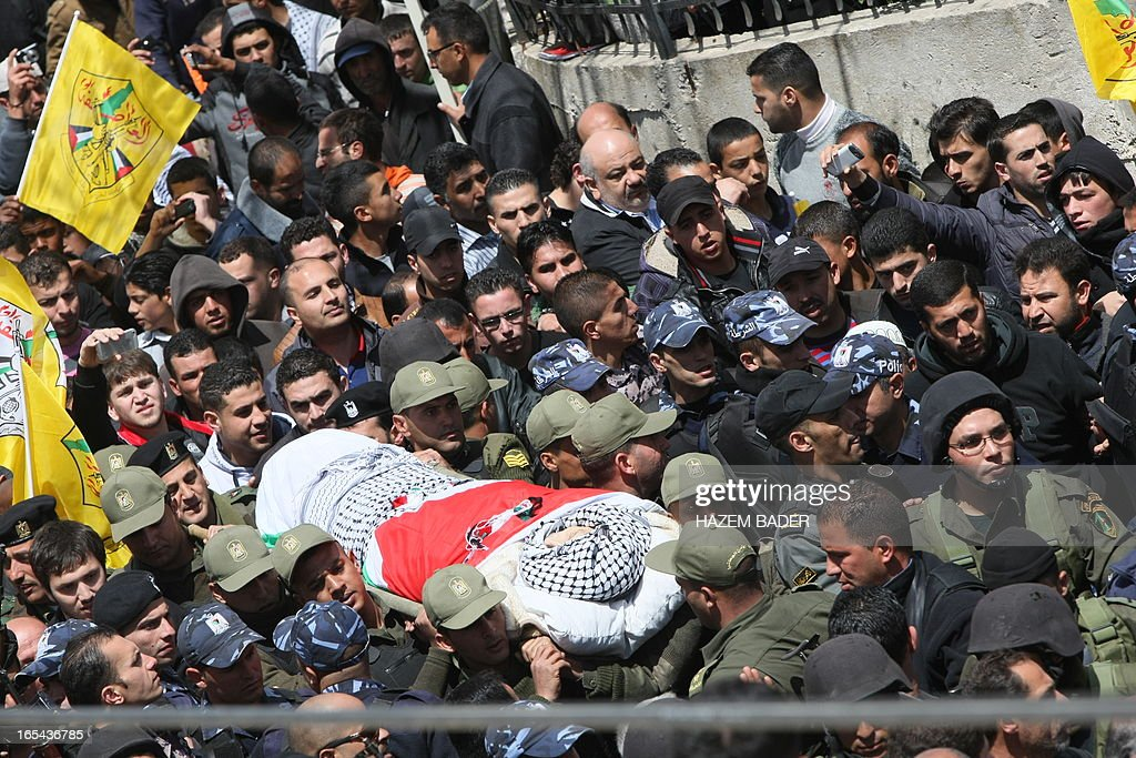 Mourners attend the funeral of Maisara Abu Hamdiya, a Palestinian prisoner who died of cancer while in Israeli detention, in the West Bank city of Hebron April 4, 2013. The West Bank simmered with anger as thousands joined the funeral of a prisoner who died in an Israeli jail and similar numbers gathered to bury two teens shot dead overnight.