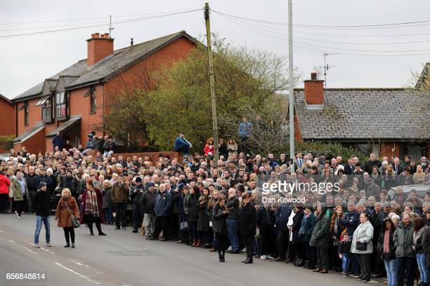 Mourners await the arrival of the coffin of the late Martin McGuinness at St Columba's Church on March 23 2017 in Londonderry Northern Ireland The...