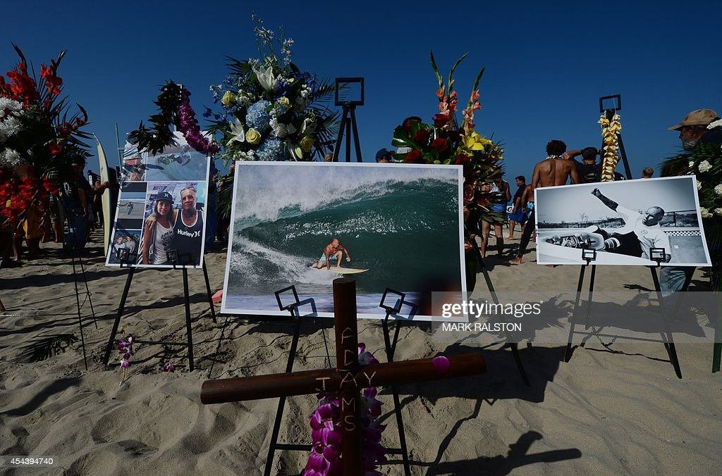 Mourners beside photos displayed for the funeral service for the pioneering and legendary skateboarder and surfer Jay Adams who died of a heart attack, at Venice Beach on August 30, 2014. Adams who became famous in the 1970's was an original member of the 'Z-Boy' skateboard team and was portrayed by actor Emile Hirsch in the film ``Lords of Dogtown'', died of a heart attack while vacationing in Mexico. AFP PHOTO/Mark RALSTON