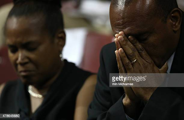 Mourners bow their heads in prayer during the funeral service where US President Barack Obama delivered the eulogy for South Carolina State senator...