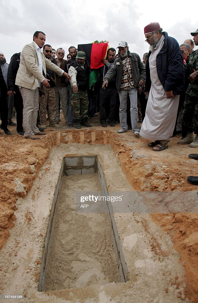 Mourners bury the coffin of leading Libyan dissident Mansour al-Kikhia during his funeral procession in the eastern Libyan port city of Benghazi on December 3, 2012. Kikhia, who disappeared 19 years ago under the Kadhafi regime, was buried, weeks after his body was found in an intelligence services morgue, his brother said.