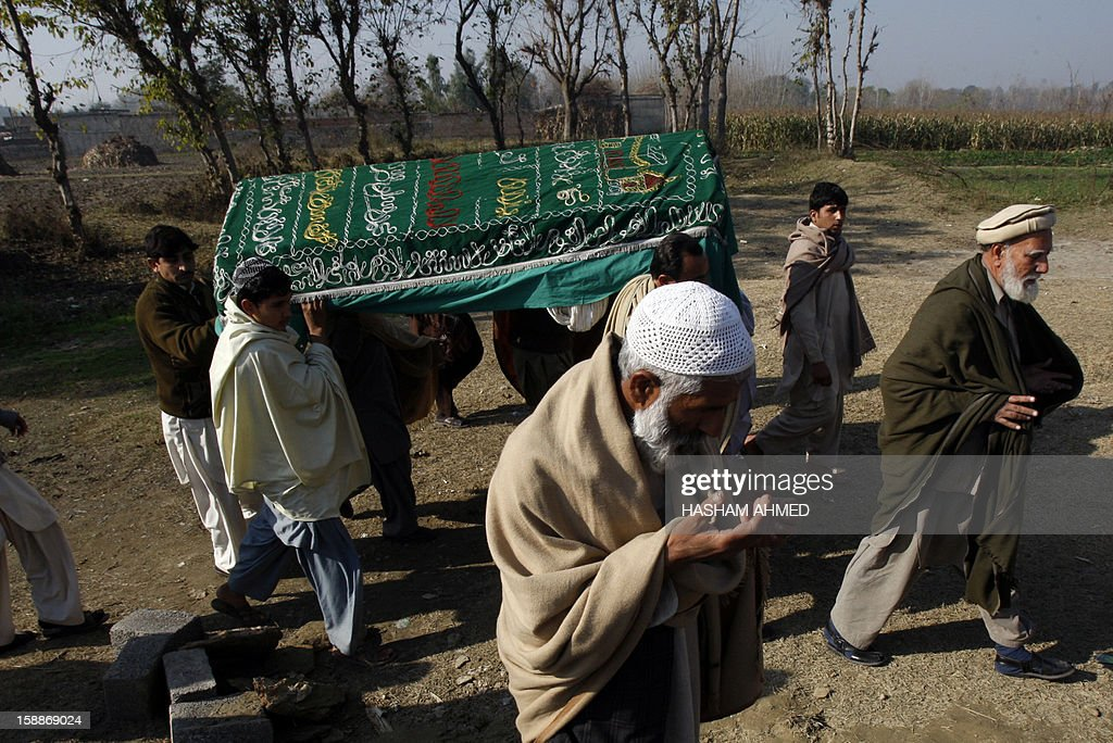 Mourners carry a coffin of a Pakistani charity worker, who was killed with other colleagues during yesterday's attack by gunmen, in Swabi on January 2, 2013. Aid groups January 2 demanded greater protection in Pakistan amid concerns of a new spike in violence after seven charity workers were shot dead and their organisation suspended operations. The six women -- five of them teachers and one a health visitor -- and a male health technician were ambushed by gunmen on motorbikes on January 1 as they were returning from a community centre in northwestern district Swabi. AFP PHOTO/HASHAM AHMED