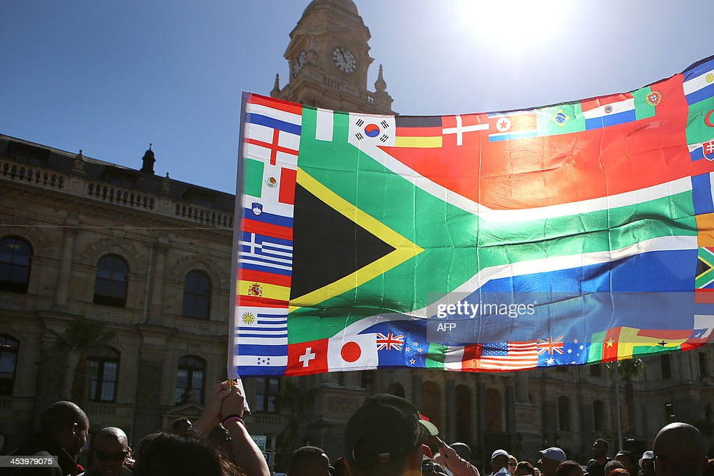 Mourners carry a South African flag surrounded by world flags as they gather to honour late South African former president Nelson Mandela at an inter-faith service on December 6, 2013, held at the Grand Parade in Cape Town, where Mandela made his first speech as a free man in 1990. Mandela, the revered icon of the anti-apartheid struggle in South Africa and one of the towering political figures of the 20th century, died in Johannesburg on December 5 at age 95. Mandela, who was elected South Africa's first black president after spending nearly three decades in prison, had been receiving treatment for a lung infection at his Johannesburg home since September, after three months in hospital in a critical state.