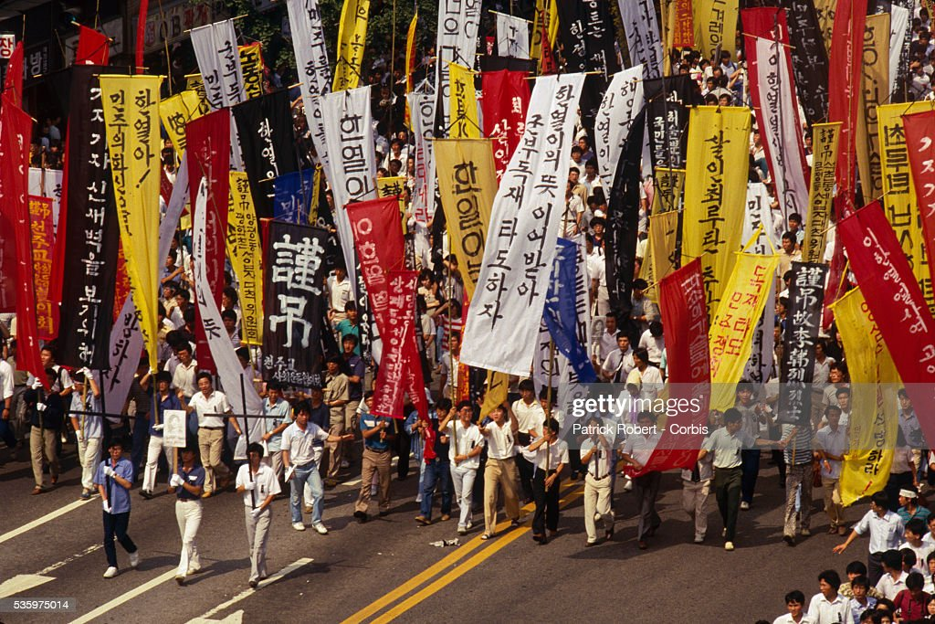 Mourners carry colorful banners in a procession at a large public funeral for a student killed in a riot in Seoul. Students and other demonstrators all over South Korea protested the political and economic situation and eventually brought the regime of President Chun Doo Hwan to an end. In October 1987, the National Assembly ratified a new constitution, which provided for direct presidential elections.