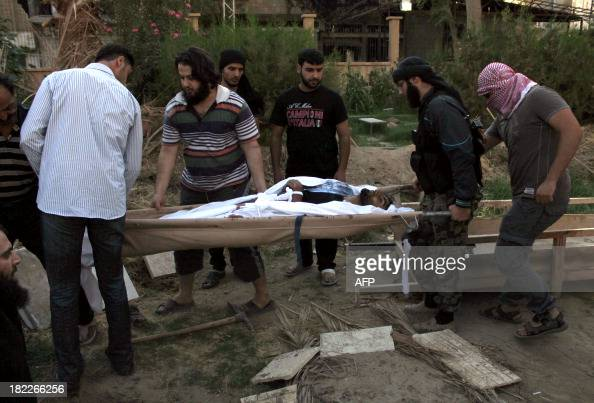 Mourners carry the body of a Syrian photojournalist and media activist Murhaf alModhi known as Abo Shuja during his funeral in a park in the northern...