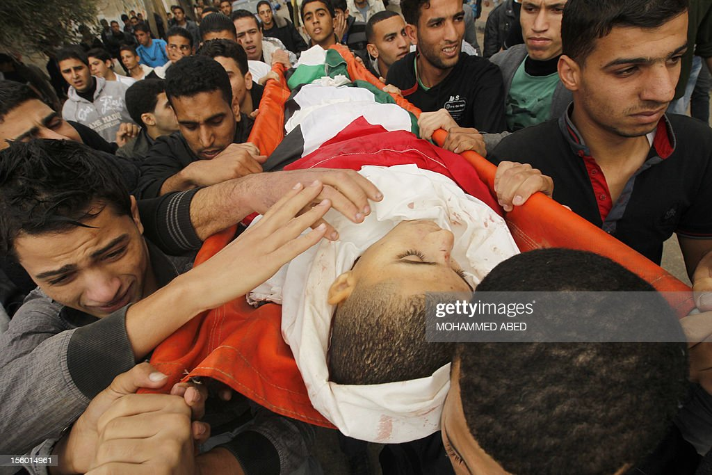 Mourners carry the body of killed Palestinian civilian Ahmad Dardasawy, 18, during his funeral in Gaza City on November 11, 2012 , the day after he was killed in Israeli shelling as clashes erupted along the Isreali-Gaza Strip border. The flare-up was one of the most serious since Israel's devastating 22-day operation in the Gaza Strip over New Year 2009.
