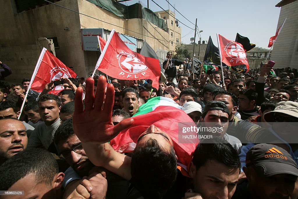 Mourners carry the body of Mahmoud Al-Titi, a Hamas militant who was killed by Israeli soldiers during clashes the previous night, and wave flags of the Popular Front for the Liberation of Palestine (PFLP) during his funeral procession in the al-Fawwar refugee camp on the outskirts of the West Bank town of Hebron on March 13, 2013. The Israeli military said that soldiers entered the Al-Fawwar refugee camp, close to the Jewish settlement of Beit Haggai, after Palestinians hurled rocks and petrol bombs at passing Israeli vehicles. AFP PHOTO / HAZEM BADER