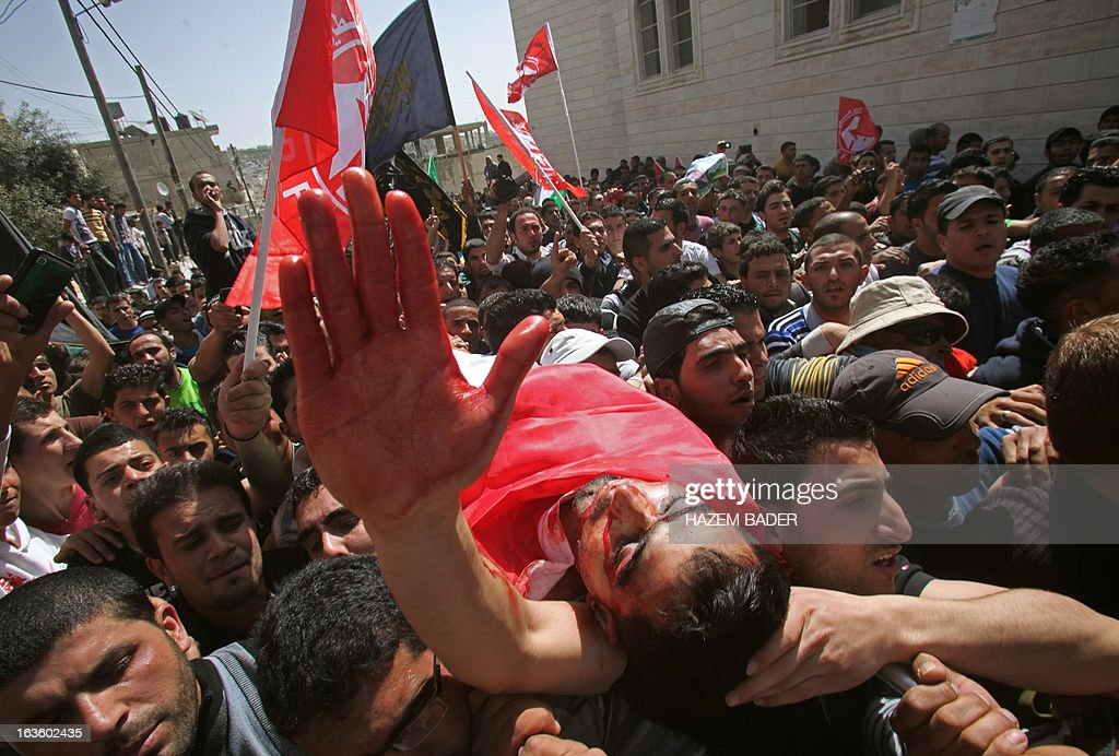 Mourners carry the body of Mahmoud Al-Titi, a Hamas militant who was killed by Israeli soldiers during clashes the previous night, during his funeral procession in the al-Fawwar refugee camp on the outskirts of the West Bank town of Hebron on March 13, 2013. The Israeli military said that soldiers entered the Al-Fawwar refugee camp, close to the Jewish settlement of Beit Haggai, after Palestinians hurled rocks and petrol bombs at passing Israeli vehicles. AFP PHOTO / HAZEM BADER