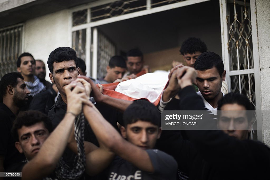 Mourners carry the body of one of the two Palestinian Al-Aqsa TV journalists killed the previous day in an Israeli air strike during their funeral in Gaza City on November 21, 2012, as fighting raged on both sides of Gaza's borders despite intensified efforts across the region to thrash out a truce to end a week of violence that has so far cost 136 Palestinian and five Israeli lives. AFP PHOTO/MARCO LONGARI