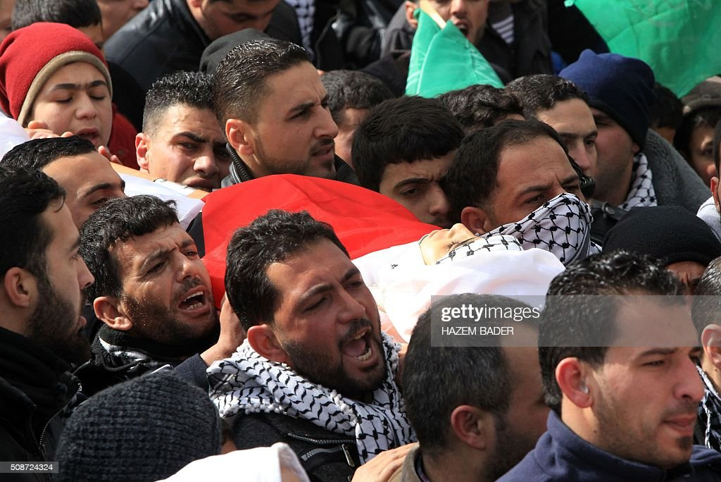 Mourners carry the body of Palestinian Haitham al-Bau, who was shot dead by Israeli soldiers after throwing a petrol bomb at a military jeep, during his funeral in the village of Halhoul north of the West Bank city of Hebron, on February 6, 2016 BADER