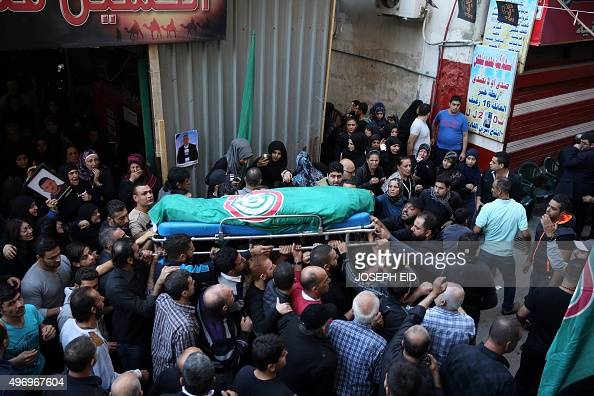 Mourners carry the body of Samer Huhu who was killed in a twin bombing attack that rocked a busy shopping street in the area of Burj alBarajneh...