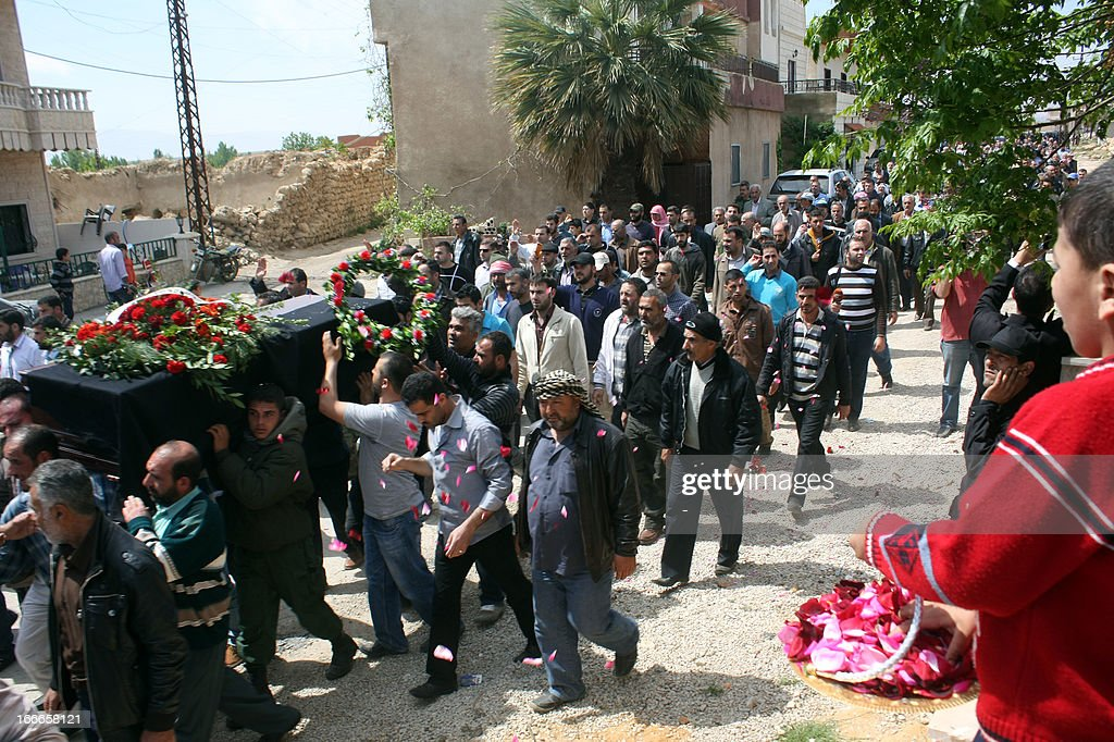 Mourners carry the coffin of a 13-year old Lebanese child who was killed when the border town of Qasr, in the Hermel border region, came under artillery shell fire from Syrian territory, during his funeral procession in the village of Hosh Sayyed Ali, on the Syrian-Lebanese border, on April 14, 2013. Lebanese President Michel Sleiman issued a statement after the incident in Qasr, condemning the fire and adding that such spillover 'has only led to the deaths of innocent Lebanese who have nothing to do with the ongoing conflict taking place outside their country.'
